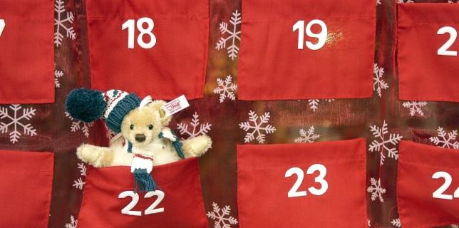 Vorweihnachtliche Dekoration im Schaufenster eines Spielwarengeschäftes. Adventskalender aus rotem Stoff mit Zahlentaschen und einem Stofftier mit Wollmütze in der Tasche des 22. Dezember, Bonn 01.11.2005.